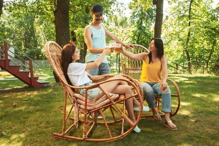Group of happy friends having beer and barbecue party at sunny day. Resting together outdoor in a forest glade or backyard. Celebrating and relaxing, laughting. Summer lifestyle, friendship concept. Stockfoto - 128551729