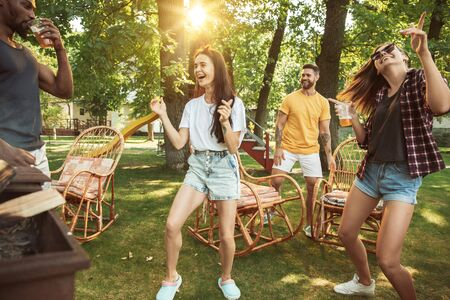Group of happy friends having beer and barbecue party at sunny day. Resting together outdoor in a forest glade or backyard. Celebrating and relaxing, laughting. Summer lifestyle, friendship concept.