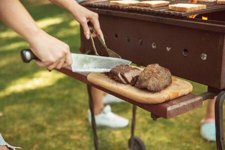 Bier- und Grillparty am sonnigen Sommertag. Nahaufnahme von Grillen Fleisch Steak im Freien in einer Waldlichtung oder im Hinterhof. Sommerlebensstil, Urlaub, Resort, Familien- oder Freundesparty, Lebensmittelkonzept.