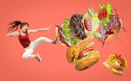 Fast food. Young caucasian woman fights with unhealthy nutrition. Kicks burger or sandwich in jump on red background. Copyspace for your ad. Creative collage about food, weight loss, healthy eating.