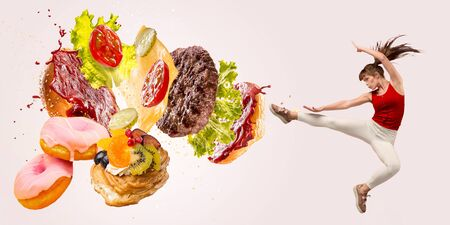 Fight the fast food. Burgers crashing by the boxer isolated on white background. Combination of buns, vegetables, sauce and cutlet is broken by sportswoman. Healthy eating, diet and sport concept. Imagens
