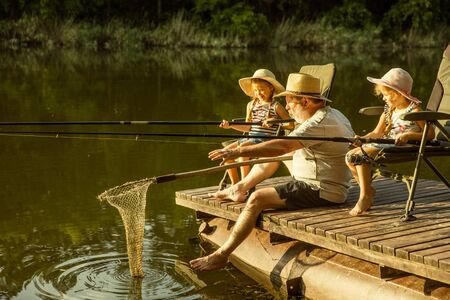 Cute little girls and their granddad are on fishing at the lake or river. Resting on pier near by water and forest in sunset time of summer day.