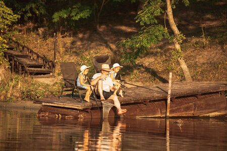 Cute little girls and their granddad are on fishing at the lake or river. Resting on pier near by water and forest in sunset time of summer day. Concept of family, recreation, childhood, nature. Banco de Imagens