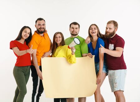 Young man and woman weared in LGBT flag colors on white background. Caucasian models in bright shirts. Look happy, smiling and hugging. LGBT pride, human rights and choice concept. Copyspace.