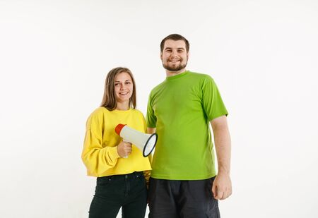 Young man and woman weared in LGBT flag colors on white background. Caucasian models in bright shirts. Look happy, smiling and hugging. LGBT pride, human rights and choice concept. Holding mouthpiece.