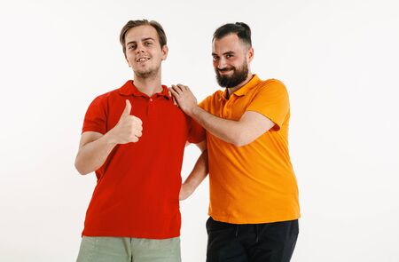 Young men weared in LGBT flag colors isolated on white background. Caucasian male models in bright shirts. Look happy, smiling and hugging. LGBT pride, human rights and choice concept. Banco de Imagens