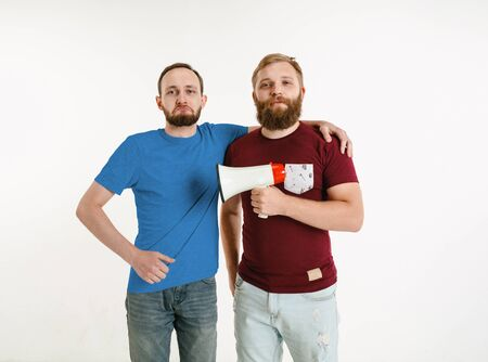 Young men weared in LGBT flag colors on white background. Caucasian male models in bright shirts. Look happy, smiling and hugging. LGBT pride, human rights and choice concept. Holding mouthpiece. Banco de Imagens