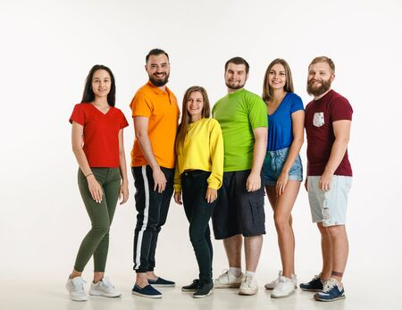 Young man and woman weared in LGBT flag colors on white background. Caucasian models in bright shirts. Look happy, smiling and hugging. LGBT pride, human rights and choice concept. Banco de Imagens