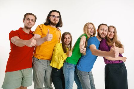 Young man and woman weared in LGBT flag colors on white background. Caucasian models in bright shirts. Look happy together, smiling and hugging. LGBT pride, human rights and choice concept.