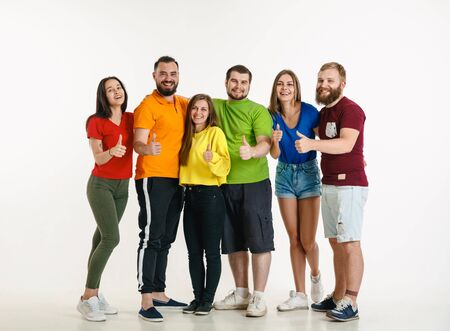 Young man and woman weared in LGBT flag colors on white background. Caucasian models in bright shirts. Look happy, smiling and hugging. LGBT pride, human rights and choice concept. Stock fotó
