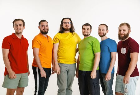 Young men weared in LGBT flag colors isolated on white background. Caucasian male models in shirts of red, orange, yellow, green, blue and purple. LGBT pride, human rights and choice concept. Banco de Imagens