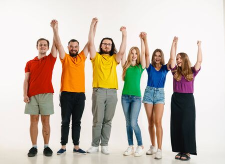 Young man and woman weared in LGBT flag colors on white background. Caucasian models in bright shirts. Look happy together, smiling, hugging. LGBT pride, human rights and choice concept. Celebrating. Banco de Imagens