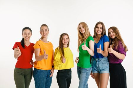 Young man and woman wear in rainbow flag colors on white background. Caucasian models in bright shirts. Look happy together