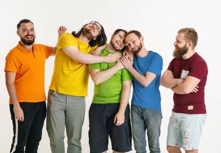 Young men wear in rainbow flag colors isolated on white background. Caucasian male models in shirts of red, orange, yellow, green, blue and purple. 写真素材 - 129274607