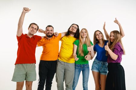 Young man and woman wear in rainbow flag colors on white background. Caucasian models in bright shirts. Look happy together, smiling, hugging.