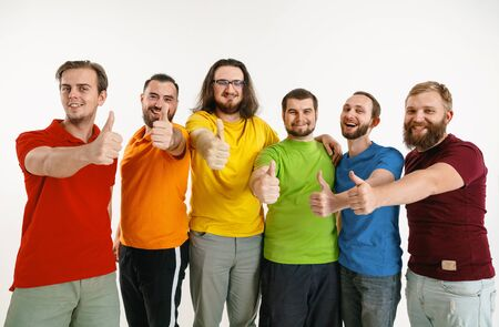 Young men wear in rainbow flag colors isolated on white background. Caucasian male models in shirts of red, orange, yellow, green, blue and purple.