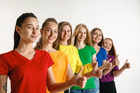 Young women wearing rainbow flag colors isolated on white background. Caucasian female models in bright shirts. Look happy, showing thumbs up. Stock fotó