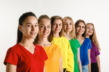 Young women wearing rainbow flag colors isolated on white background. Caucasian female models in bright shirts. Look happy, smiling.