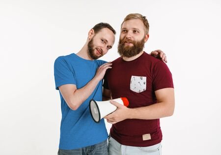 Young men wear in rainbow flag colors on white background. Caucasian male models in bright shirts. Look happy, smiling and hugging. Stock fotó