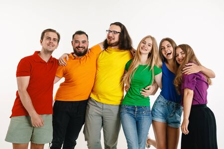 Young man and woman wear in rainbow flag colors on white background. Caucasian models in bright shirts. Look happy together, smiling and hugging.