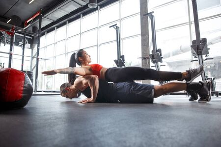 A muscular athletes doing workout at the gym. Gymnastics, training, fitness workout flexibility. Active and healthy lifestyle, youth, bodybuilding. Doing exercises together, training in push ups.