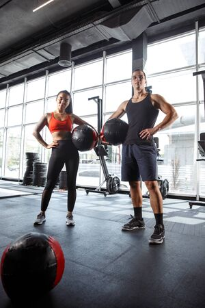 A muscular athletes doing workout at the gym. Gymnastics, training, fitness workout flexibility. Active and healthy lifestyle, youth, bodybuilding. Doing exercises, standing with the fit balls.