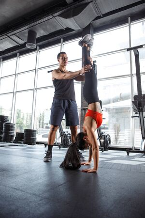 A muscular athletes doing workout at the gym. Gymnastics, training, fitness workout flexibility. Active and healthy lifestyle, youth, bodybuilding. Doing exercises for holding balance.