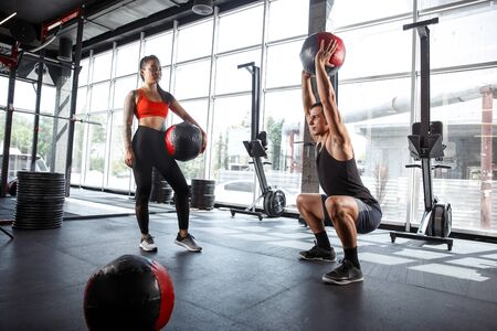 A muscular athletes doing workout at the gym. Gymnastics, training, fitness workout flexibility. Active and healthy lifestyle, youth, bodybuilding. Doing exercises, training in squats with the ball.