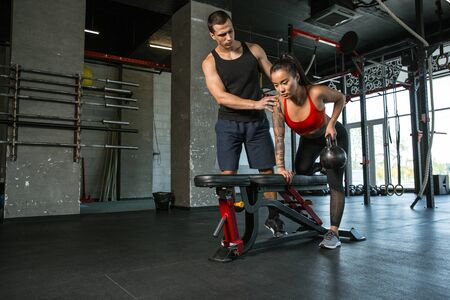 A muscular athletes doing workout at the gym. Gymnastics, training, fitness workout flexibility. Active and healthy lifestyle, youth, bodybuilding. Doing exercises with weights, training upper body. Stok Fotoğraf