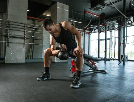 A muscular athlete doing workout at the gym. Gymnastics, training, fitness workout flexibility. Active and healthy lifestyle, youth, bodybuilding. Doing exercises, training upper body with the weight. Standard-Bild - 128868213