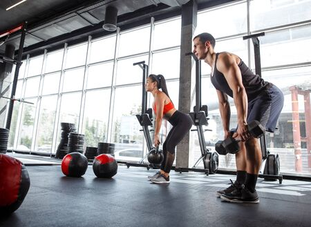 A muscular athletes doing workout at the gym. Gymnastics, training, fitness workout flexibility. Active and healthy lifestyle, youth, bodybuilding. Doing exercises together, training upper body. Standard-Bild - 128868214