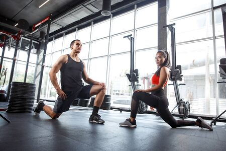 A muscular athletes doing workout at the gym. Gymnastics, training, fitness workout flexibility. Active and healthy lifestyle, youth, bodybuilding. Training in lunges and stretching exercises. Imagens
