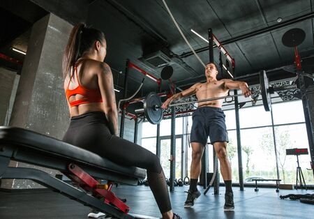 A muscular athletes doing workout at the gym. Gymnastics, training, fitness workout flexibility. Active and healthy lifestyle, youth, bodybuilding. Doing exercises with barbell, training upper body. Stok Fotoğraf