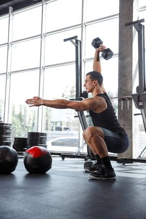 A muscular athlete doing workout at the gym. Gymnastics, training, fitness workout flexibility. Active and healthy lifestyle, youth, bodybuilding. Doing exercises, training in squats with the weight.