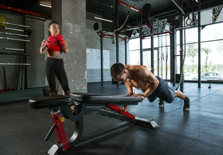 A muscular athletes doing workout at the gym. Gymnastics, training, fitness workout flexibility. Active and healthy lifestyle, youth, bodybuilding. Doing exercises together, training upper body. Standard-Bild - 128871047