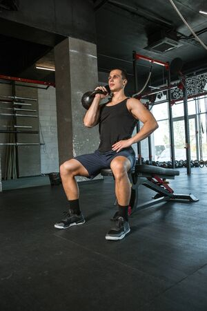A muscular athlete doing workout at the gym. Gymnastics, training, fitness workout flexibility. Active and healthy lifestyle, youth, bodybuilding. Doing exercises, training upper body with the weight. 写真素材 - 128871042