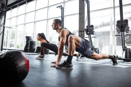 A muscular athletes doing workout at the gym. Gymnastics, training, fitness workout flexibility. Active and healthy lifestyle, youth, bodybuilding. Training in lunges and stretching exercises. 写真素材 - 128871063