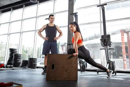 A muscular athletes doing workout at the gym. Gymnastics, training, fitness workout flexibility. Active and healthy lifestyle, youth, bodybuilding. Doing exercises together, training in jump with box. Imagens