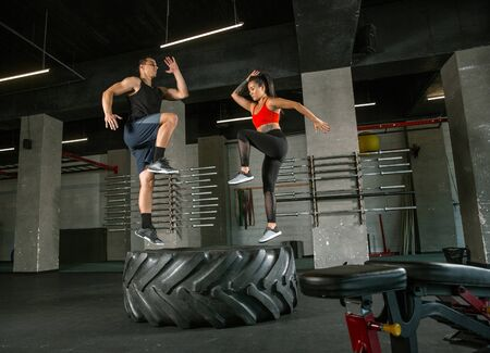 A muscular athletes doing workout at the gym. Gymnastics, training, fitness workout flexibility. Active and healthy lifestyle, youth, bodybuilding. Doing exercises together, training with the tire.