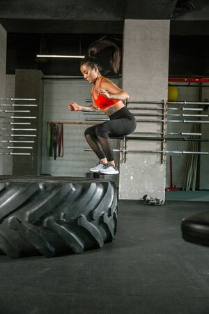 A muscular athlete doing workout at the gym. Gymnastics, training, fitness workout flexibility. Active and healthy lifestyle, youth, bodybuilding. Doing exercises, training in squats with the tire. 写真素材 - 128871073