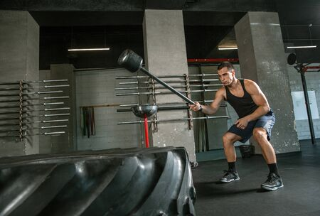 A muscular male athlete doing workout at the gym. Gymnastics, training, fitness workout flexibility. Active and healthy lifestyle, youth, bodybuilding. Doing exercises, training with the tire. 写真素材 - 128871722