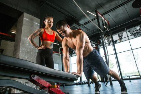 A muscular athletes doing workout at the gym. Gymnastics, training, fitness workout flexibility. Active and healthy lifestyle, youth, bodybuilding. Doing exercises together, training upper body. Stok Fotoğraf