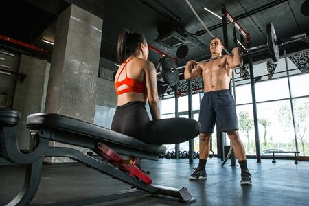 A muscular athletes doing workout at the gym. Gymnastics, training, fitness workout flexibility. Active and healthy lifestyle, youth, bodybuilding. Doing exercises with barbell, training upper body. Standard-Bild - 128871721