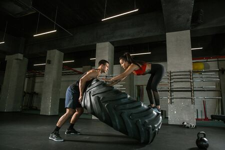 A muscular athletes doing workout at the gym. Gymnastics, training, fitness workout flexibility. Active and healthy lifestyle, youth, bodybuilding. Doing exercises together, training with the tire. 写真素材 - 128871719