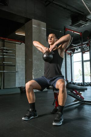 A muscular athlete doing workout at the gym. Gymnastics, training, fitness workout flexibility. Active and healthy lifestyle, youth, bodybuilding. Doing exercises, training upper body with the weight. Standard-Bild - 128871735