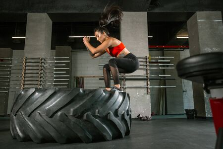 A muscular athlete doing workout at the gym. Gymnastics, training, fitness workout flexibility. Active and healthy lifestyle, youth, bodybuilding. Doing exercises, training in squats with the tire.