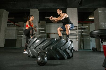 A muscular athletes doing workout at the gym. Gymnastics, training, fitness workout flexibility. Active and healthy lifestyle, youth, bodybuilding. Doing exercises together, training with the tire. 写真素材 - 128871741