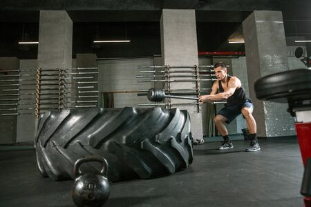 A muscular male athlete doing workout at the gym. Gymnastics, training, fitness workout flexibility. Active and healthy lifestyle, youth, bodybuilding. Doing exercises, training with the tire.