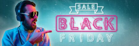 Black friday, sales, purchases concept. Neon lighted letters on gradient background. Astonished man pointing. Negative space. Modern design. Contemporary art. Creative conceptual and colorful collage.