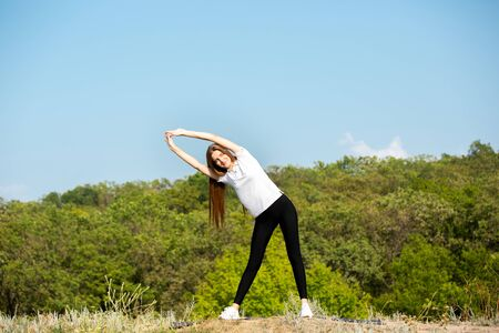 Beautiful young caucasian woman in sportswear training flexibility outdoors on green meadow against forest view in sunny day. Healthy lifestyle, sport, activity, movement concept. Looks full of energy. 版權商用圖片